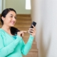 a woman smiling holding her phone | On Target Home Inspection | Home Security Orland Park