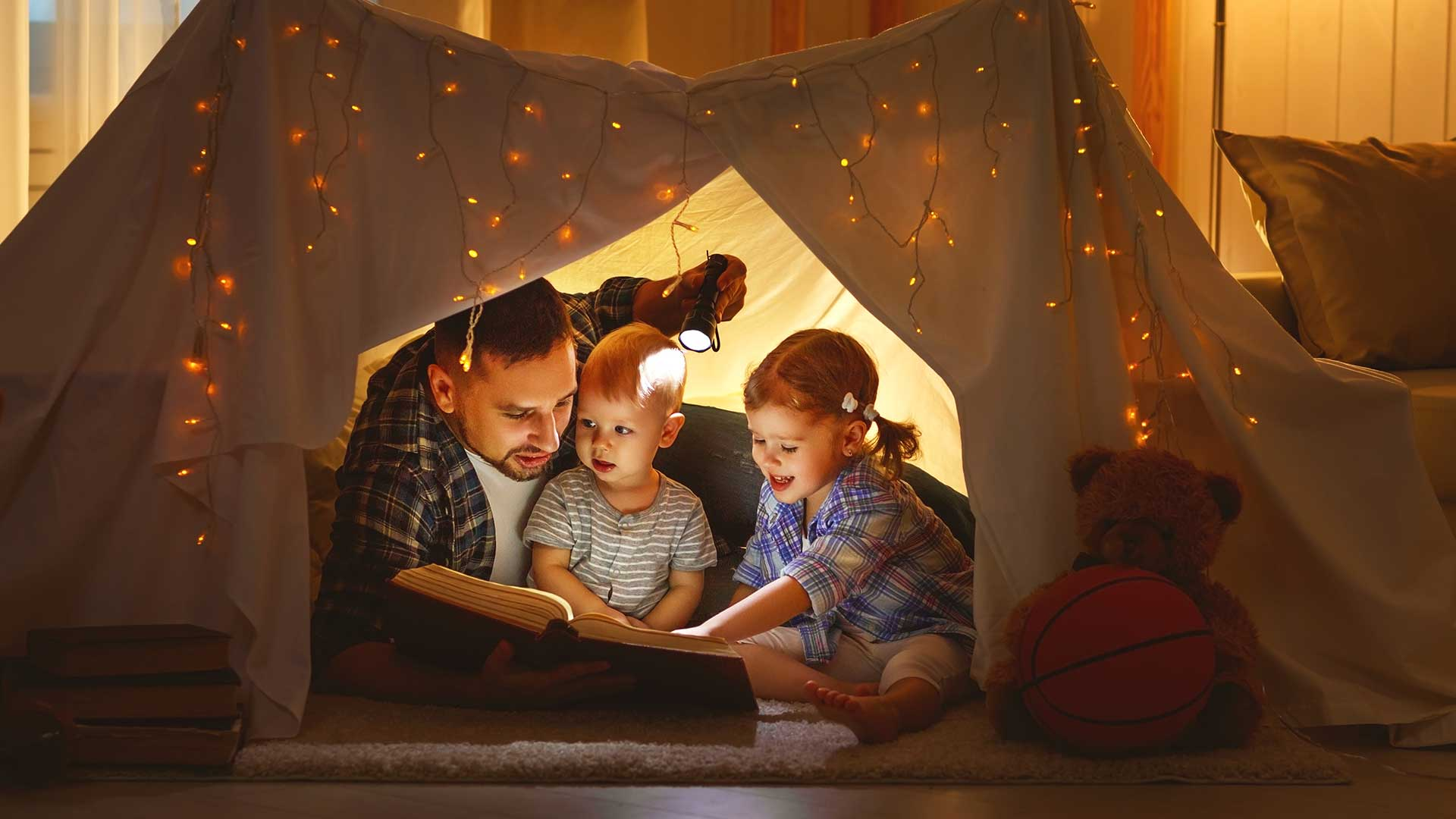 Family reading book in homemade fort